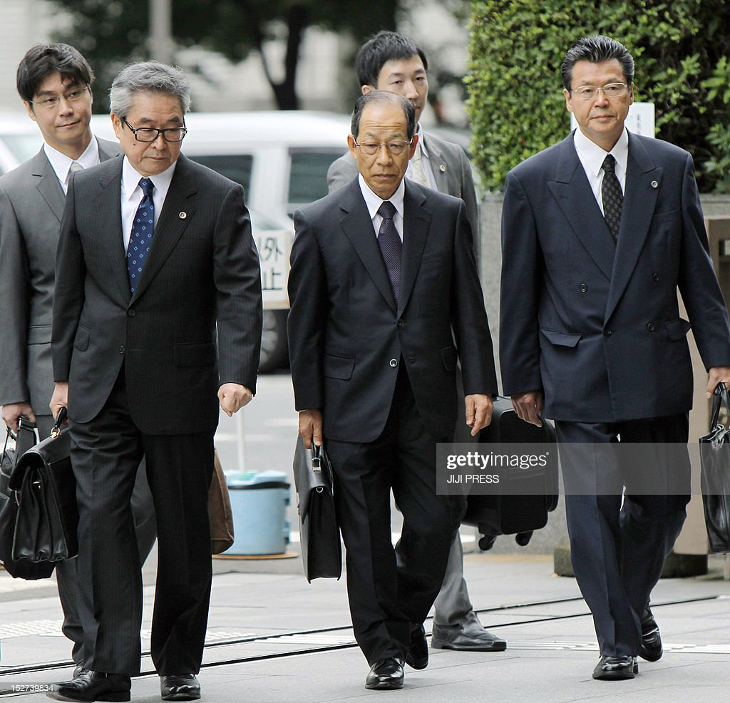 Former Olympus chairman Tsuyoshi Kikukawa (C), accompanied by his lawyers, enters the Tokyo District Court for his first hearing of the trial in Tokyo on September 25, 2012. Scandal-wracked Olympus and three of its former top executives pleaded guilty in court over charges that they deliberately hid losses worth 1.7 billion USD after a series of bad investments. ikukawa apologised in Tokyo District Court and said he would take 'full responsibility' for the crime that came to light when his British successor blew the whistle roughly a year ago. AFP PHOTO / JIJI PRESS JAPAN OUT