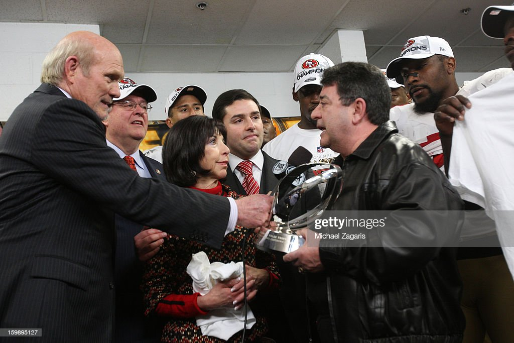Former owner Eddie Debartolo of the San Francisco 49ers presents the George Halas Trophy to his sister and team Co-Chairman Denise York along nephew and team CEO Jed York, former in the locker room following the game against Atlanta Falcons in the NFC Championship game at the Georgia Dome on January 20, 2013 in Atlanta, Georgia. The 49ers defeated the Falcons 28-24.