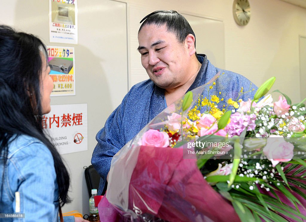 Former Ozeki (second highest rank in sumo) Miyabiyama receives a flower bunch from a fan during a press conference on his retirement at Osaka Prefecture Gymnasium on March 24, 2013 in Osaka, Japan.