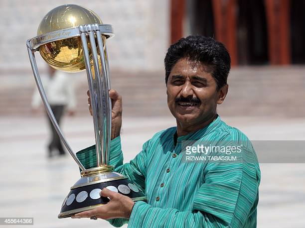 Former Pakistan cricketer Javed Miandad poses for a photograph with the ICC World Cup 2015 trophy during a ceremony at the mausoleum of the country's...