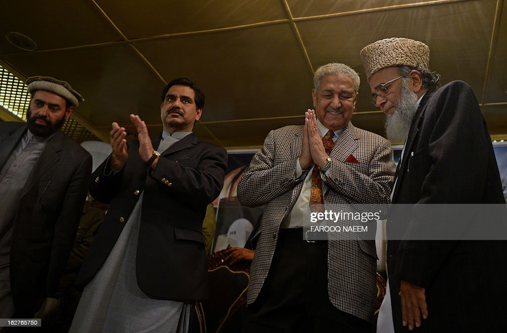 Former Pakistani nuclear scientist and chairman of Tehreek-e-Tahafuz Pakistan party, Abdul Qadeer Khan (2R), claps as Syed Munawar Hassan (R) President of Jamaat-e-Islami party stands to give a speech during a public meeting in Islamabad on February 26, 2013. Khan has registered a new political party last year to contest for the first time general elections expected next year, officials said. AFP PHOTO/Farooq NAEEM