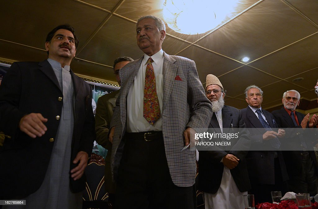 Former Pakistani nuclear scientist and chairman of Tehreek-e-Tahafuz Pakistan party, Abdul Qadeer Khan (2L), stands to give a speech during a public meeting in Islamabad on February 26, 2013. Khan has registered a new political party last year to contest for the first time general elections expected next year, officials said. AFP PHOTO/Farooq NAEEM