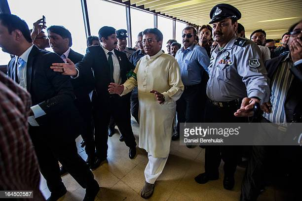 Former Pakistani president Pervez Musharraf is ushered through by security after landing on Pakistani soil at Jinnah International airport on March...