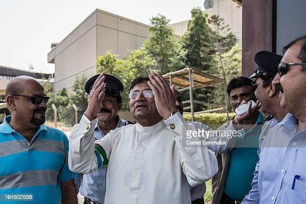 Former Pakistani president Pervez Musharraf raises his hand in prayer as he looks to the sky after landing on Pakistani soil at Jinnah International...