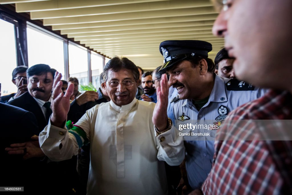 Former Pakistani president, <a gi-track='captionPersonalityLinkClicked' href=/galleries/search?phrase=Pervez+Musharraf&family=editorial&specificpeople=121550 ng-click='$event.stopPropagation()'>Pervez Musharraf</a> raises his hands in thanks as he is greeted by supporters and ushered through by security after landing on Pakistani soil, at Jinnah International airport on March 24, 2013 in Karachi, Pakistan. The former Pakistani president and military ruler returned to Pakistan after 4 years of self-imposed exile to participate in historic elections in May. Mr Musharraf has been granted protective bail in several cases, including conspiracy to murder which has paved his way allowing for his return.