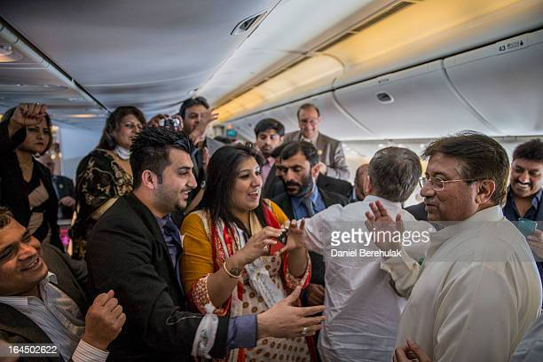 Former Pakistani president Pervez Musharraf walks through the cabin as he greets his All Pakistan Muslim League party supporters on his Emirates...