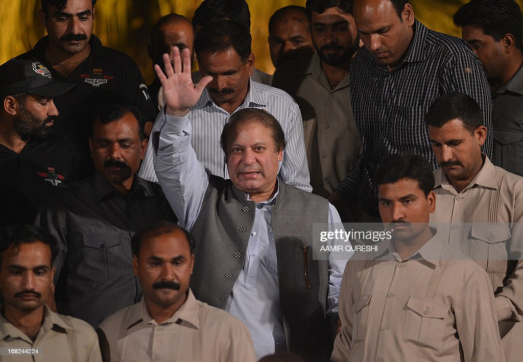 Former Pakistani Prime Minister Nawaz Sharif is escorted by his security personnel as he waves to supporters while he leaves after an election campaign meeting in Rawalpindi on May 7, 2013. The election will mark a democratic milestone in a country ruled for half its history by the military. It will be the first time that a civilian government has served a full term and handed over to another at the ballot box.