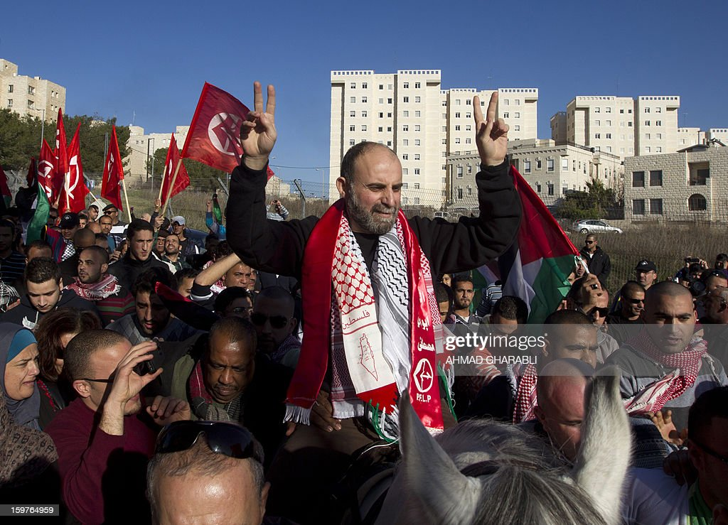 Former Palestinian prisoner Jihad Abedi flashes the V-sign for victory as he rides on a horse through a neighborhood of Jeruslaem following his release on January 20, 2013, from an Israeli jail after serving 25 years.