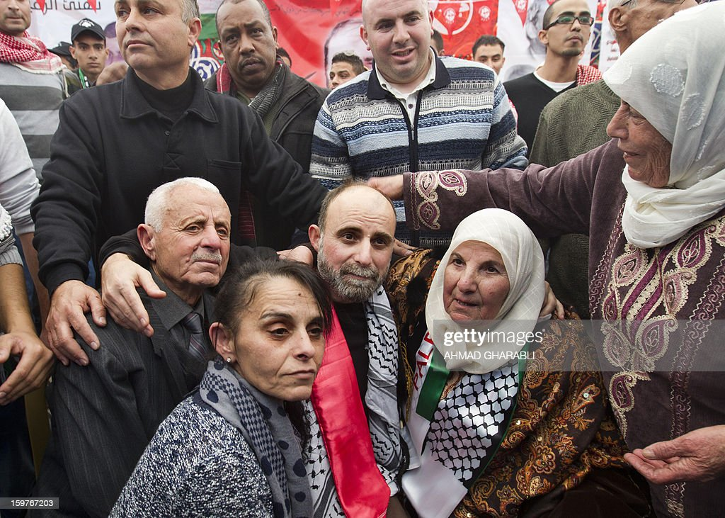 Former Palestinian prisoner Jihad Abedi (C) is surrounded by his mother (R), father and sister (front) as he arrives in a neighborhood of Jerusalem following his release from an Israeli jail after serving 25 years, on January 20, 2013. AFP PHOTO/AHMAD GHARABLI