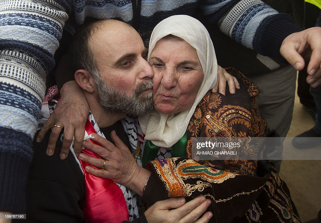 Former Palestinian prisoner Jihad Abedi (R) kisses his mother as he arrives in a neighborhood of Jerusalem following his release from an Israeli jail after serving a 25 year sentence, on January 20, 2013. AFP PHOTO/AHMAD GHARABLI