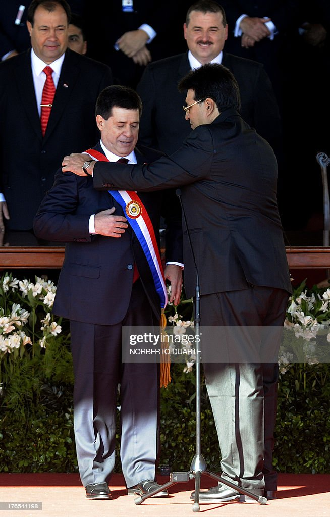 Former Paraguayan president Federico Franco straightens the presidential sash to President elect Horacio Cartes during the inauguration ceremony in...