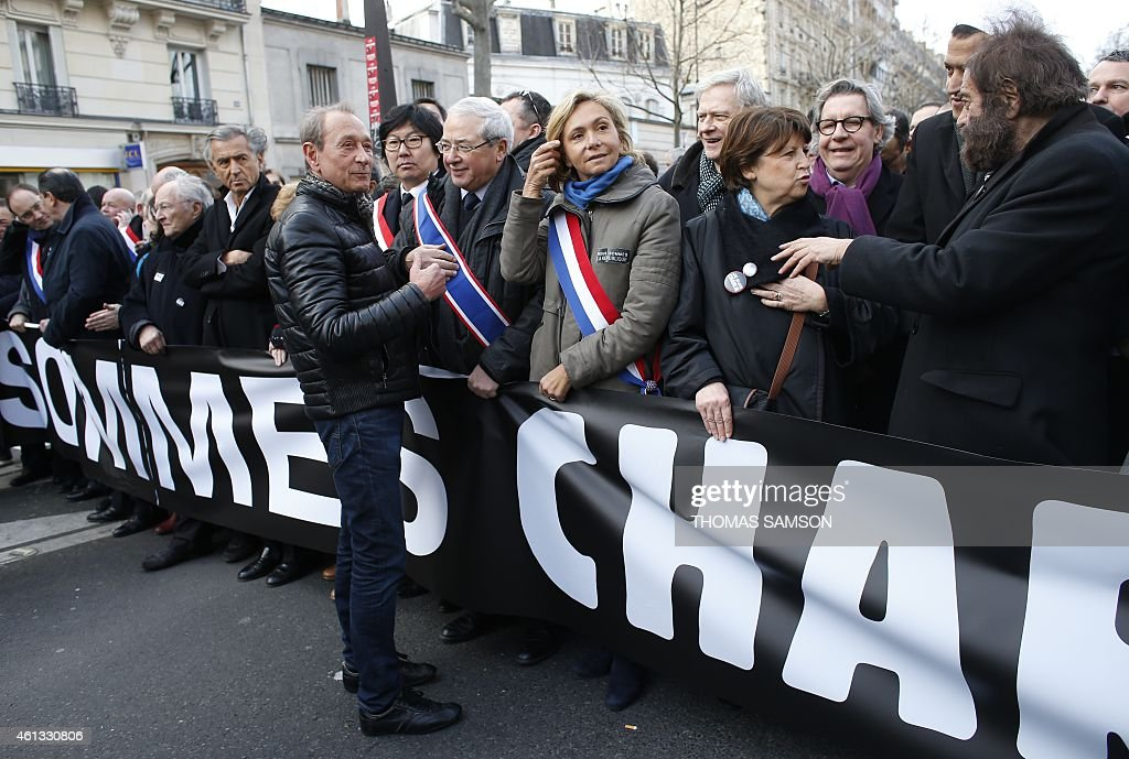 Former Paris' Mayor <a gi-track='captionPersonalityLinkClicked' href=/galleries/search?phrase=Bertrand+Delanoe&family=editorial&specificpeople=206163 ng-click='$event.stopPropagation()'>Bertrand Delanoe</a> (C) talks with <a gi-track='captionPersonalityLinkClicked' href=/galleries/search?phrase=Jean-Paul+Huchon&family=editorial&specificpeople=543988 ng-click='$event.stopPropagation()'>Jean-Paul Huchon</a> (C, R), President of the Ile de France region, UMP right-wing party member Valerie Pecresse, the Mayor of Lille and Socialist Party member <a gi-track='captionPersonalityLinkClicked' href=/galleries/search?phrase=Martine+Aubry&family=editorial&specificpeople=590991 ng-click='$event.stopPropagation()'>Martine Aubry</a>, Hassen Chalghoumi, Imam of the northern Paris suburb of Drancy and president of the French Association of Imams and French writer Marek Halter while standing behind a banner reading 'Nous sommes Charlie' (We are Charlie) as they gather in Paris before the start of a Unity rally Marche Republicaine on January 11, 2015 in tribute to the 17 victims of a three-day killing spree by homegrown Islamists. The killings began on January 7 with an assault on the Charlie Hebdo satirical magazine in Paris that saw two brothers massacre 12 people including some of the country's best-known cartoonists, the killing of a policewoman and the storming of a Jewish supermarket on the eastern fringes of the capital which killed 4 local residents. AFP PHOTO / THOMAS SAMSON
