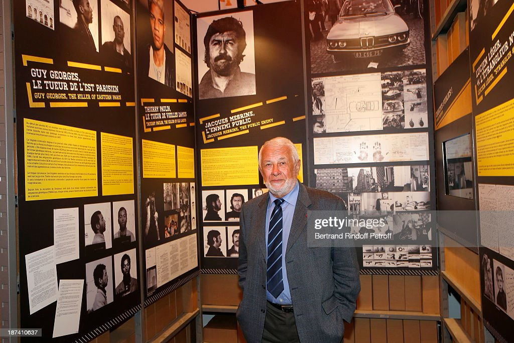 Former Paris Police chief Robert Broussard poses as he attends the '100th Anniversary Of The Paris Judiciary Police' exhibition opening on November 8, 2013 in Paris, France. A photo of criminal Jacques Mesrine (with moustache), whom Broussard contributed to locate and kill in a 1979 famed operation in Paris, is seen top center.