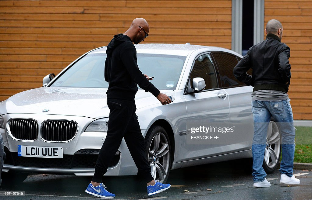 Former Paris Saint-Germain player Nicolas Anelka (C) leaves after attending a training in Saint-Germain-en-Laye, west of Paris, on December 3, 2012 on the eve of a UEFA Champions League Group A football match against Porto.