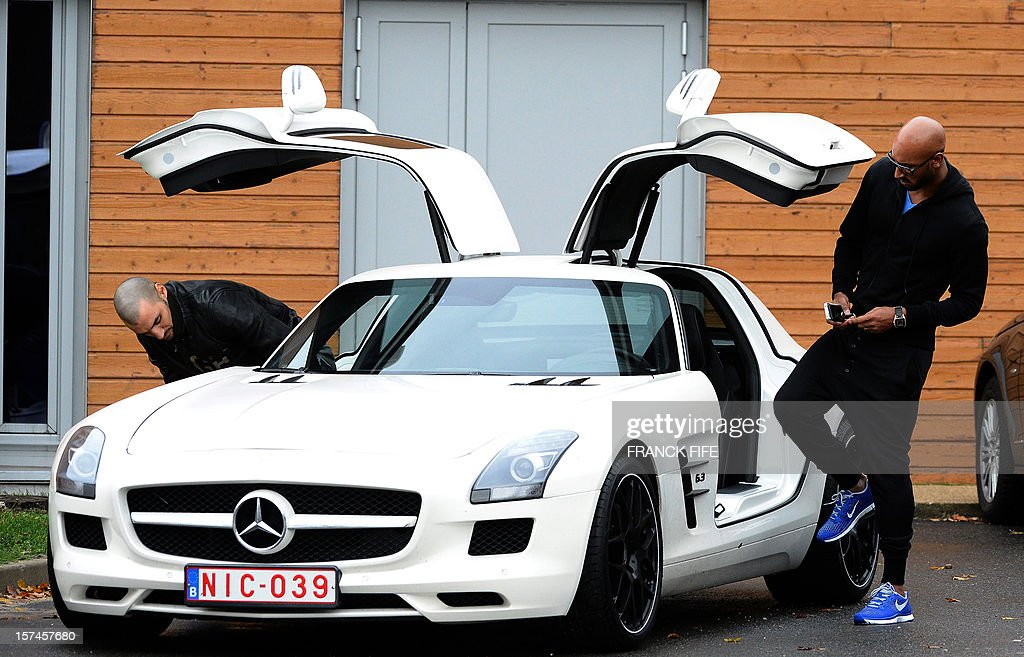 Former Paris Saint-Germain player Nicolas Anelka (R) leaves after attending a training in Saint-Germain-en-Laye, west of Paris, on December 3, 2012 on the eve of a UEFA Champions League Group A football match against Porto.