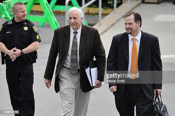 Former Penn State assistant football coach Jerry Sandusky and Karl Rominger an attorney assisting Joe Amendola walk out of the Centre County...