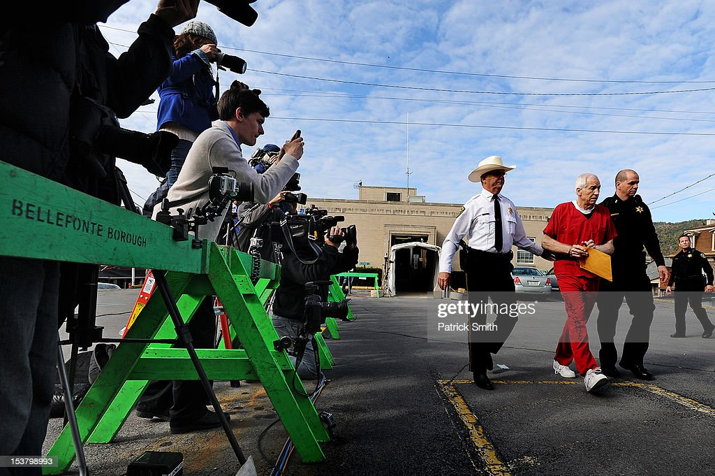 Former Penn State assistant football coach Jerry Sandusky (2nd R) leaves the Centre County Courthouse after being sentenced in his child sex abuse case on October 9, 2012 in Bellefonte, Pennsylvania. The 68-year-old Sandusky was sentenced to at least 30 years and not more that 60 years in prison for his conviction in June on 45 counts of child sexual abuse, including while he was the defensive coordinator for the Penn State college football team.