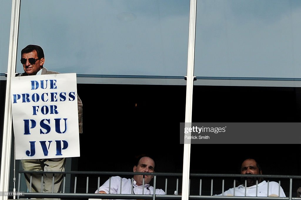 Former Penn State Nittany Lion football player Franco Harris (far right), sits with a cardboard cutout of former Penn State football coach Joe Paterno in his sky box with a sign reading 'Due Process for PSU JVP' during play between the Penn State Nittany Lions and the Ohio University Bobcats at Beaver Stadium on September 1, 2012 in State College, Pennsylvania.