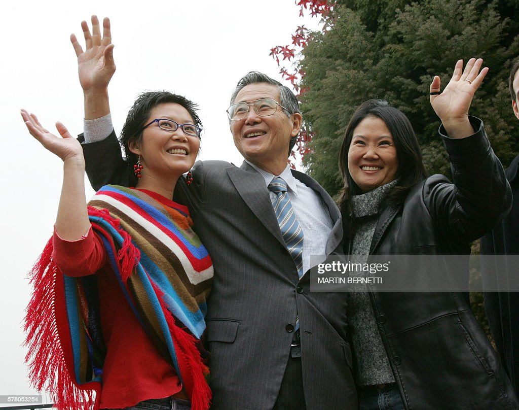 Former Peruvian President Alberto Fujimori flanked by his daughters Sachi and Keiko wave to reporters at his residence 20 May 2006 in Santiago...