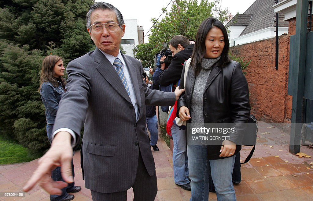 Former Peruvian President Alberto Fujimori welcomes his daughter and congresswoman Keiko at his residence 20 May 2006 in Santiago Fujimori facing...