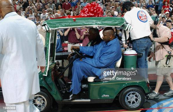Former Philadelphia 76ers greats Moses Malone and Julius Erving drive a golf cart onto the court to present it to Michael Jordan of the Washington...