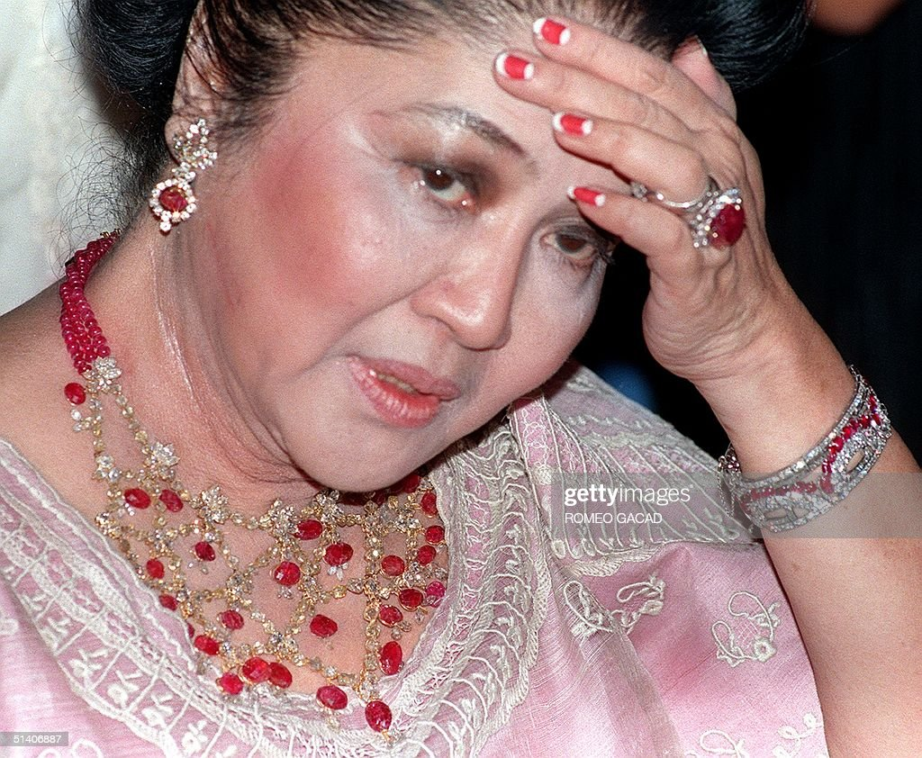 Former Philippine first lady <a gi-track='captionPersonalityLinkClicked' href=/galleries/search?phrase=Imelda+Marcos&family=editorial&specificpeople=217389 ng-click='$event.stopPropagation()'>Imelda Marcos</a>, adorned with ruby and diamond studded gold jewellery at her 70th birthday party at the luxury hotel in Manila, late 02 July 1999. The biggest party in Manila was packed with more than 1,000 glittering guests, while hundreds of her supporters waited outside. The widow of the late dictator Ferdinand Marcos has dodged jail on fraud and tax evasion charges after she and her husband were overthrown by popular revolt in 1986 after having been in power for 20 years. AFP PHOTO ROMEO GACAD/rg