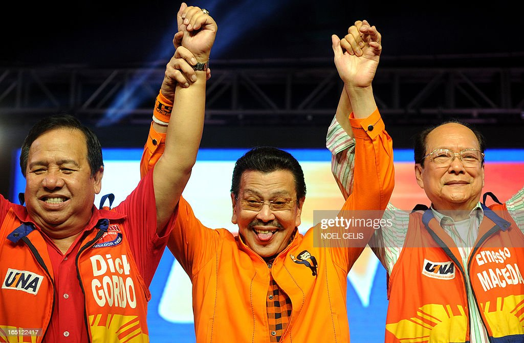 Former Philippine president and candidate for mayor of Manila Joseph Estrada (C) sticks out his tongue as he raises senatorial candidates' hands during Estrada's campaign launch on March 31, 2013 in Manila. In typically colourful fashion, graft-tainted former Philippine president Joseph Estrada launched his campaign for mayor of Manila Sunday in what he described as his 'last hurrah' in politics. The one-time movie actor, who turns 76 on April 19, said he wanted to end his political career as the mayor of a city where he was born and in whose sprawling slums he remains hugely popular. AFP PHOTO / NOEL CELIS
