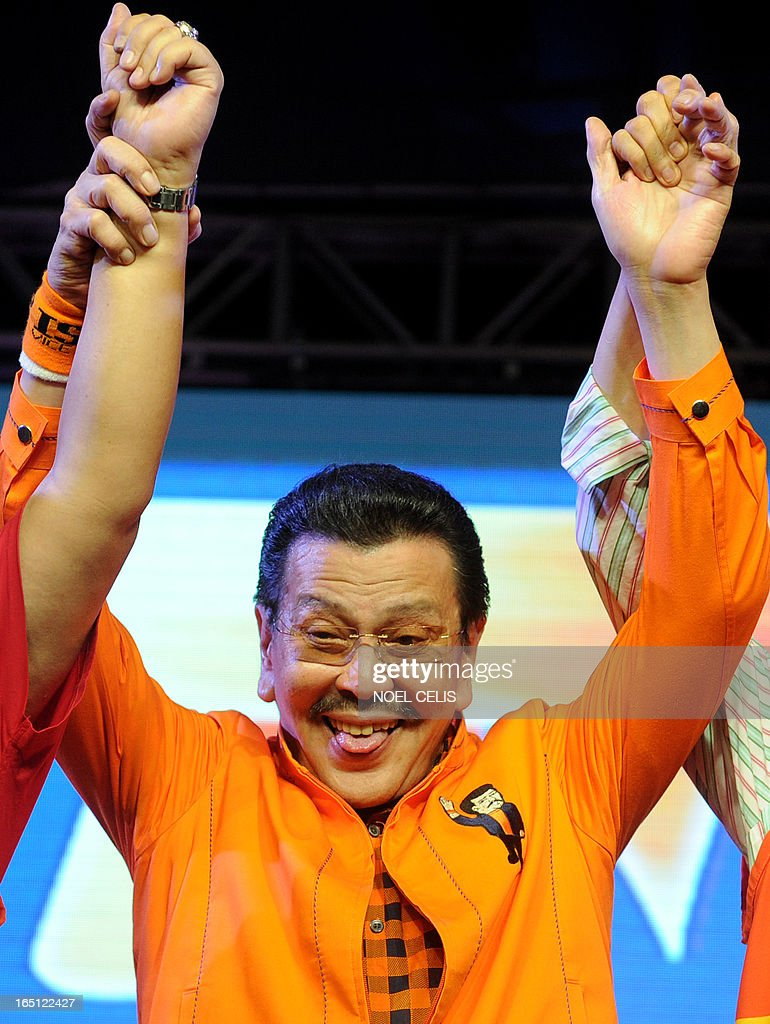 Former Philippine president and candidate for mayor of Manila Joseph Estrada (C) sticks out his tongue as he raises senatorial candidates' hands during Estrada's campaign launch on March 31, 2013 in Manila. In typically colourful fashion, graft-tainted former Philippine president Joseph Estrada launched his campaign for mayor of Manila Sunday in what he described as his 'last hurrah' in politics. The one-time movie actor, who turns 76 on April 19, said he wanted to end his political career as the mayor of a city where he was born and in whose sprawling slums he remains hugely popular.