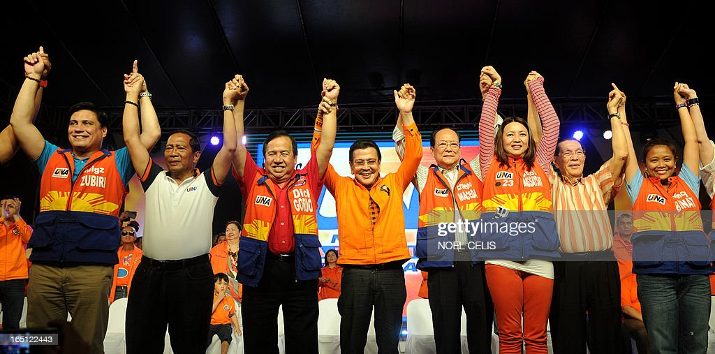 Former Philippine president and candidate for mayor of Manila Joseph Estrada (C) raises senatorial candidates' hands during Estrada's campaign launch on March 31, 2013 in Manila. In typically colourful fashion, graft-tainted former Philippine president Joseph Estrada launched his campaign for mayor of Manila Sunday in what he described as his 'last hurrah' in politics. The one-time movie actor, who turns 76 on April 19, said he wanted to end his political career as the mayor of a city where he was born and in whose sprawling slums he remains hugely popular. AFP PHOTO / NOEL CELIS