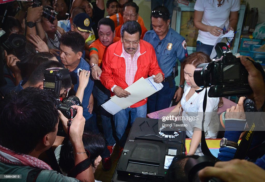 Former Philippine president <a gi-track='captionPersonalityLinkClicked' href=/galleries/search?phrase=Joseph+Estrada&family=editorial&specificpeople=553277 ng-click='$event.stopPropagation()'>Joseph Estrada</a> (C) casts his vote on May 13, 2013 in Manila, Philippines. The former president and movie actor, who was deposed in a popular revolt in 2001 and put under house arrest and eventually pardoned, is running for a mayoralty post in the city of Manila. Millions of Filipinos are casting their votes for the mid-term elections to determine their choice candidates for local posts as well as the Upper and Lower House of the Philippine Congress. So far, over 50 people have been killed in the run up to polling day for the elections that have been marred by violence and accusations of corruption and neopotism.