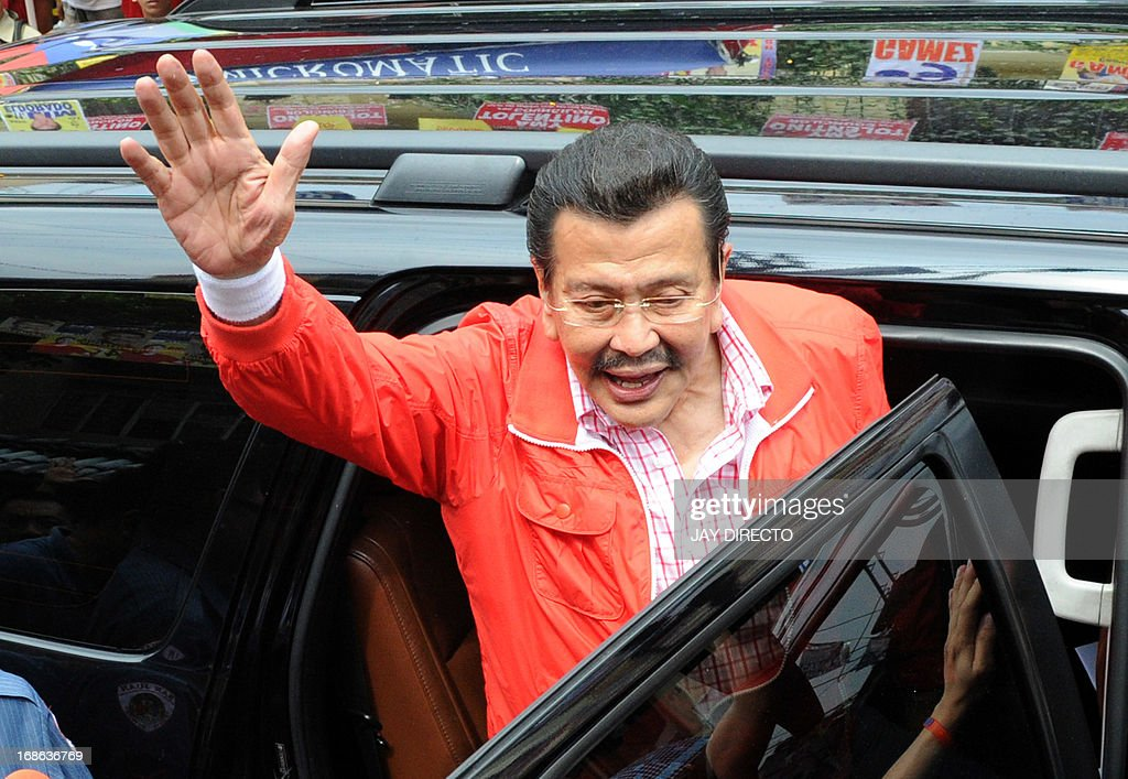 Former Philippine president Joseph Estrada (C) waves to his supporters after casting his vote during mid-term elections in Manila on May 13, 3013. The Philippines goes to the polls on May 13 to choose thousands of local leaders plus national legislators in what is seen as a referendum on the presidency of reformist Benigno Aquino. AFP PHOTO / Jay DIRECTO
