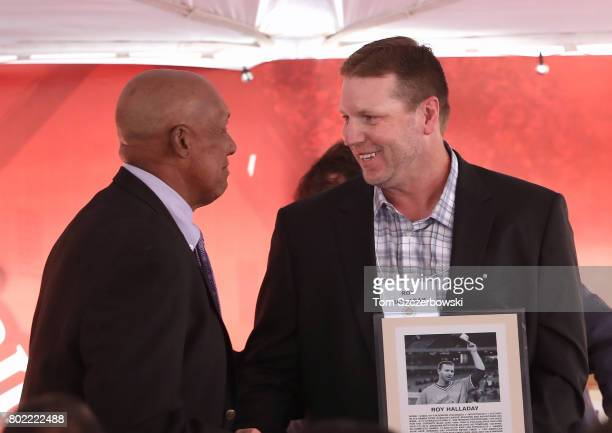 Former pitcher Roy Halladay of the Toronto Blue Jays is presented with a plaque by former pitcher Ferguson Jenkins as he is honored during the...