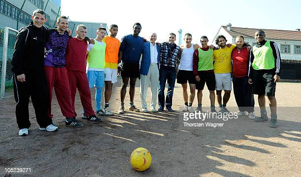 Former player and 1954 world champion Horst Eckel and 1996 European champion Stefan Kuntz pose for the media with young prisoners during a visit of...