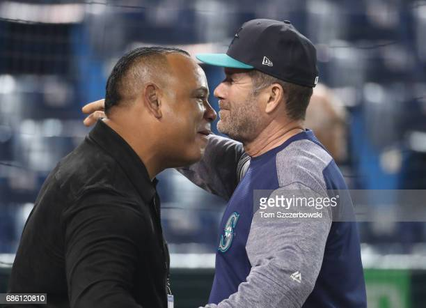Former player Carlos Baerga is greeted by hitting coach Edgar Martinez of the Seattle Mariners during batting practice before the start of the MLB...