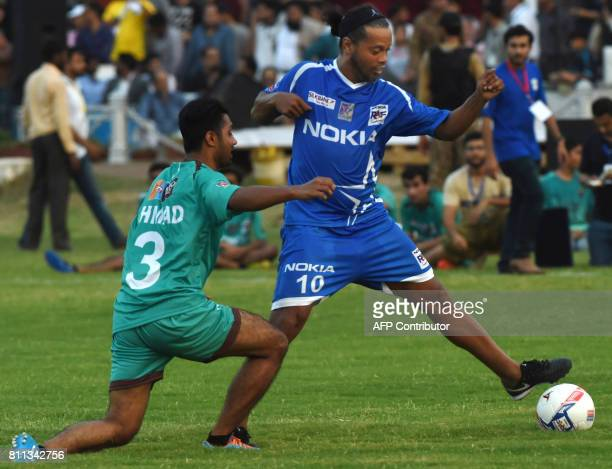 Former player for FC Barcelona Brazilian Ronaldinho vies with Pakistani football players during a friendly match on July 9 2017 in Lahore Eight of...