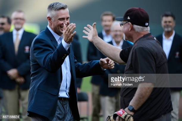 Former player for the Minnesota Twins Michael Cuddyer shakes hands with former Minnesota Twins manager and current bench coach Ron Gardenhire of the...