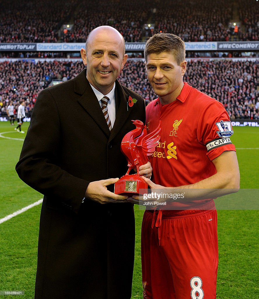 Former player Gary McAllister presents Liverpool captain Steven Gerrard with a trophy in honour of his 600th appearance for the club before the Barclays Premier League match between Liverpool and Newcastle United at Anfield on November 4, 2012 in Liverpool, England.