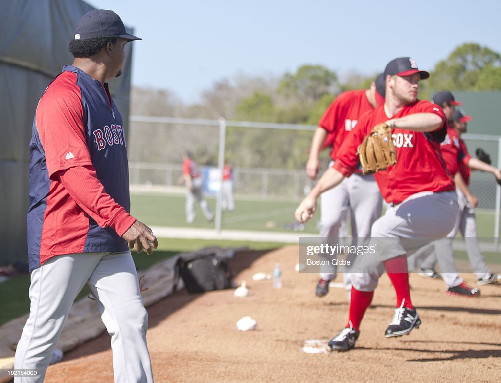 Former player Pedro Martinez, now special assistant to the general manager, walks by and watches as pitcher Andrew Bailey throws during spring training at JetBlue Park on Tuesday, Feb. 19, 2013.