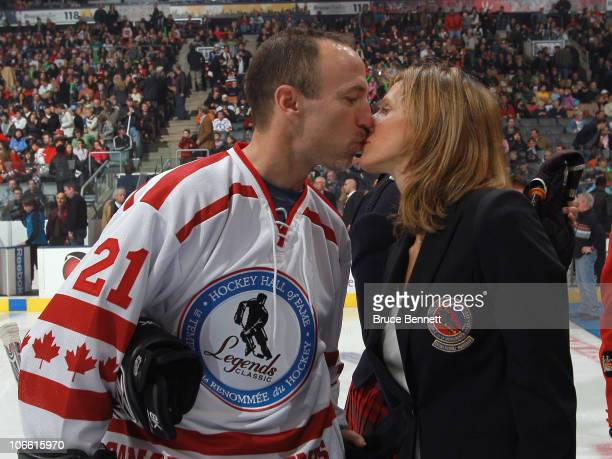 Former player Ray Ferraro and husband of Cammi Granato gives her a kiss following the Hockey Hall of Fame blazer ceremony prior to the Legends...