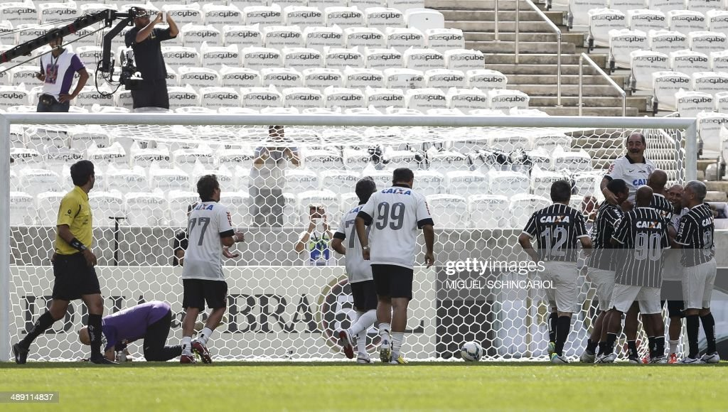 Former players celebrate a goal during a match test at the Arena Corinthians stadium on May 10, 2014 in Sao Paulo, Brazil. The Arena Corinthians will host the opening match of the FIFA World Cup Brazil 2014 between Brazil and Croatia on June 12. AFP PHOTO/Miguel SCHINCARIOL