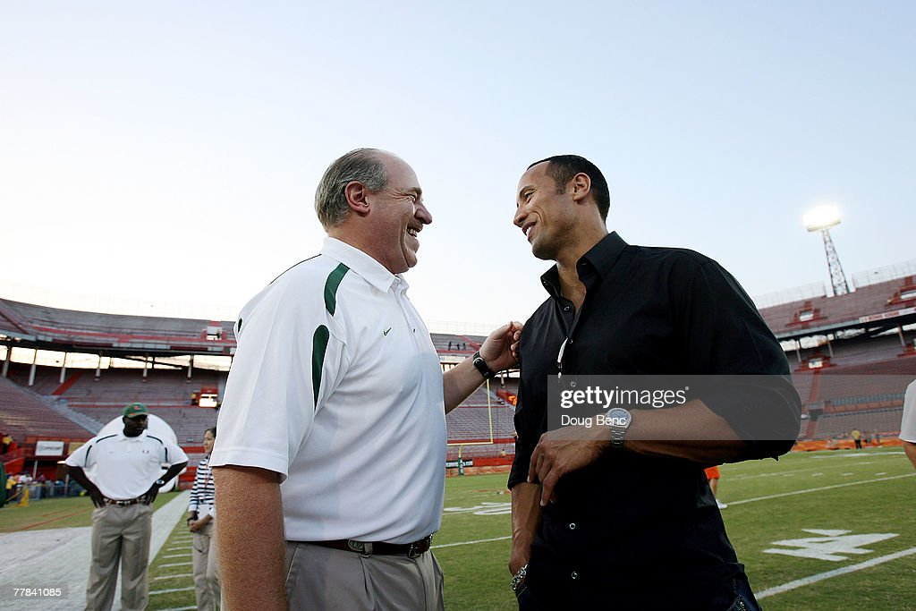 Former players Ed Hudak and Dwayne 'The Rock' Johnson talk on the field before the last college football game played in the Orange Bowl as the...