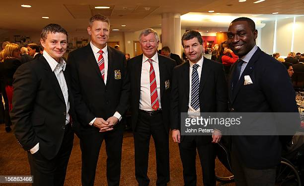 Former players Ole Gunnar Solskjaer Peter Schmeichel Denis Irwin and Andrew Cole talk with Sir Alex Ferguson after the unveiling of a statue of...