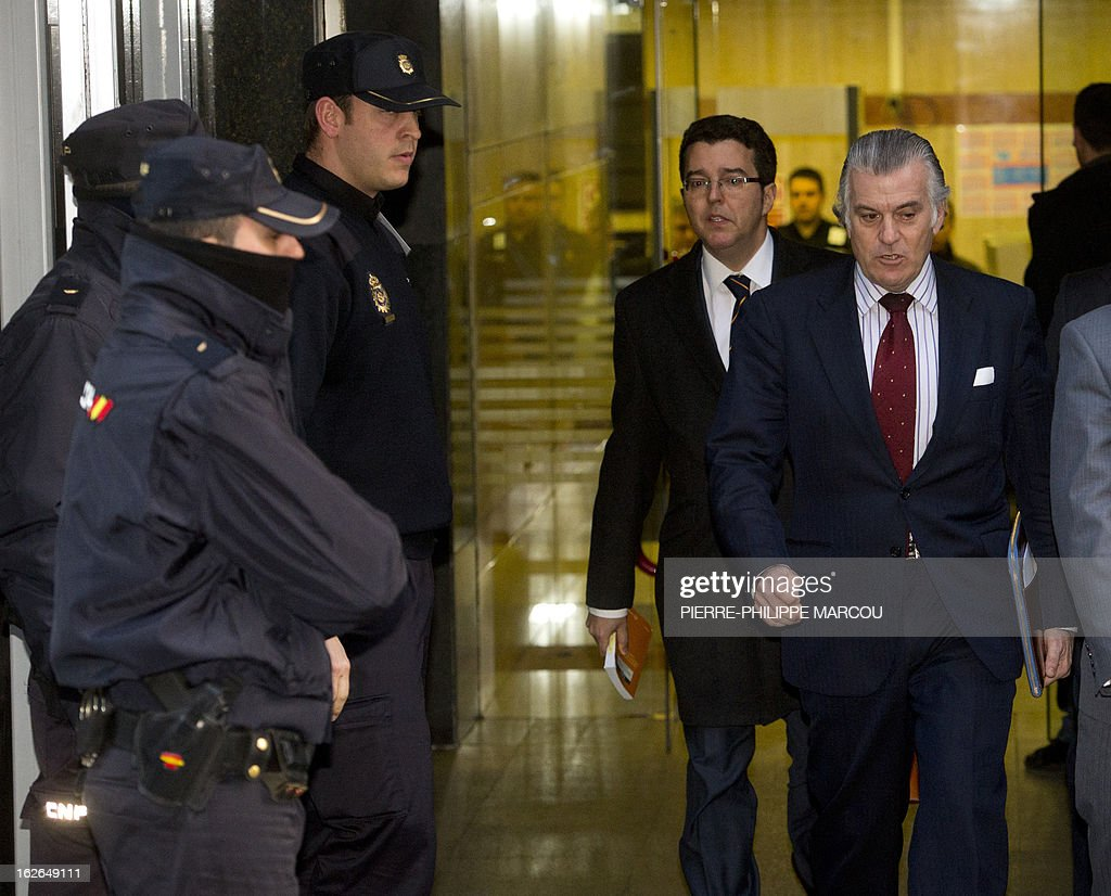 Former PP (Popular Party)'s treasurer Luis Barcenas (R), flanked by his lawyer Alfonso Trallero (2nd R), walks past police officers as he leaves the National Court in Madrid, after being questioned about the origin of 22 million euros (29 million USD) he amassed in a Swiss bank account, an amount he reportedly concealed from Spanish tax authorities, on February 25, 2013. Barcenas, who served for one year as the right-leaning party's treasurer and 19 as its assistant treasurer, is under investigation following reports that he had stashed up to 22 million euros (29 million USD) in Swiss bank accounts until 2009. AFP PHOTO/ PIERRE-PHILIPPE MARCOU