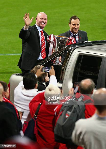Former premiership winning Swans players Barry Hall and Jude Bolton wave to the crowd during a lap of honour prior to the round 13 AFL match between...