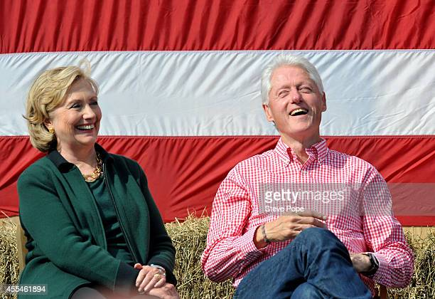 Former President Bill Clinton and his wife former Secretary of State Hillary Rodham Clinton laugh during a speech by US Sen Tom Harkin during the...