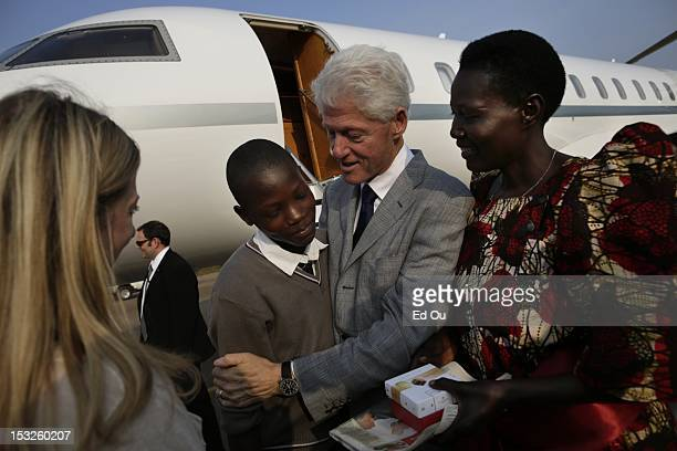 Former President Bill Clinton embraces his namesake Bill Clinton Kaligani at the airport in Entebbe Uganda on July 20 with his mother and Chelsea...