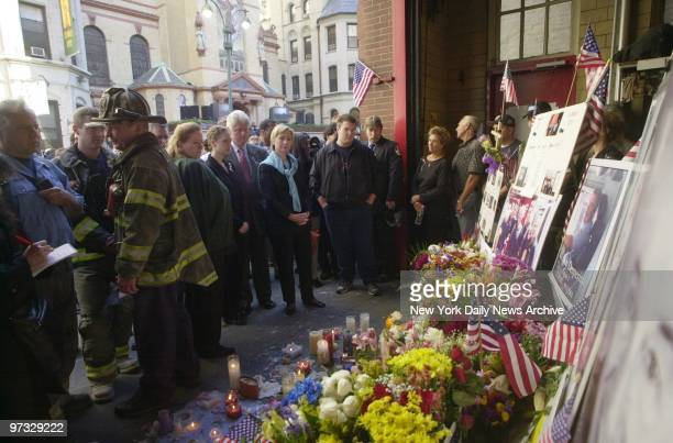Former President Bill Clinton joined by daughter Chelsea and wife Sen Hillary Rodham Clinton stands with firefighters in front of a memorial to their...