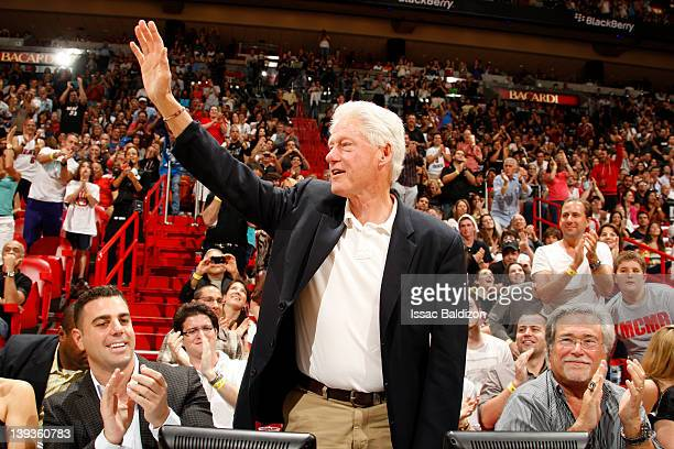 Former President Bill Clinton waves to the crowd during the game between the Orlando Magic and Miami Heat on February 19 2012 at American Airlines...