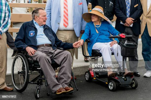 Former President George HW Bush and first lady Barbara Bush hold hands and talk before the dedication of the Mathew J Lanigan bridge that connects...