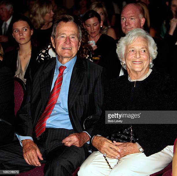 Former President George HW Bush left along with wife Barbara Bush sit on the front row as they await for their granddaughter designer Lauren Bush to...